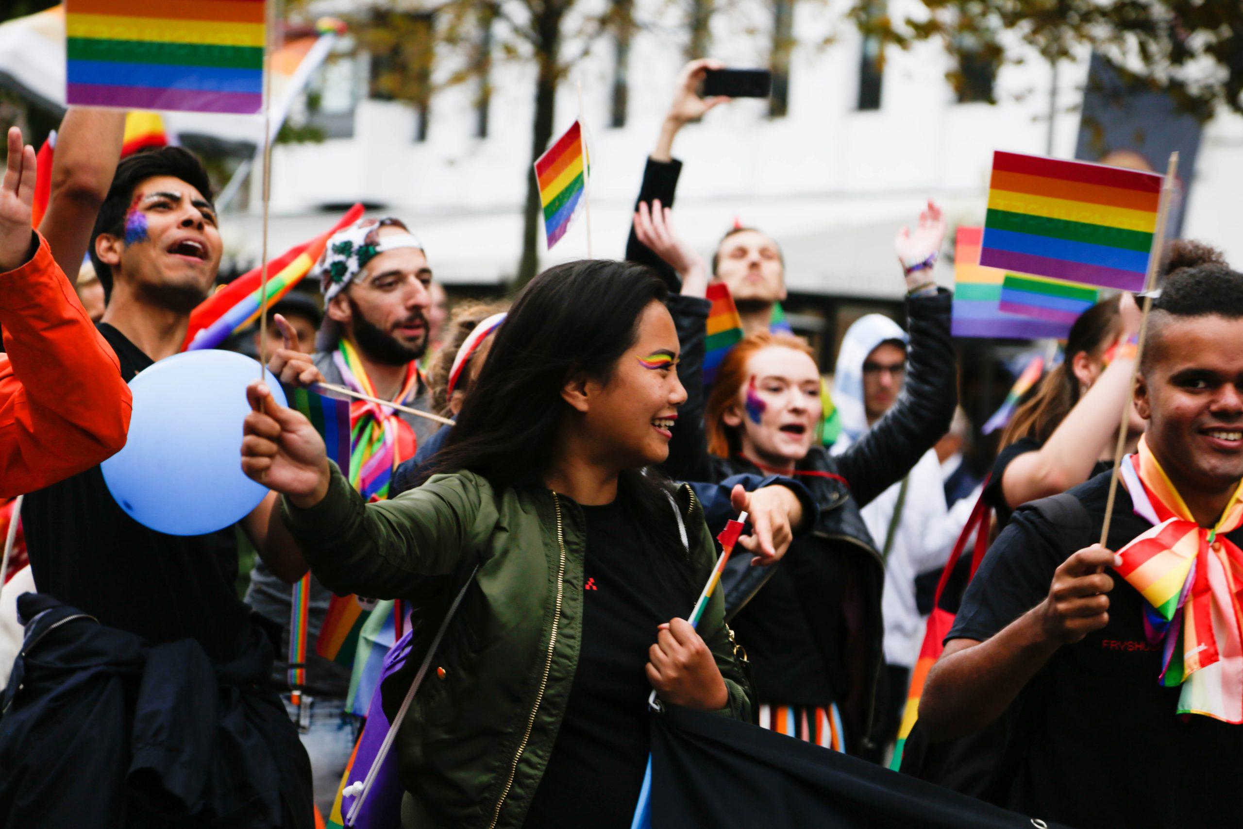 glada personer i paraden flaggar med regnbågsflaggan