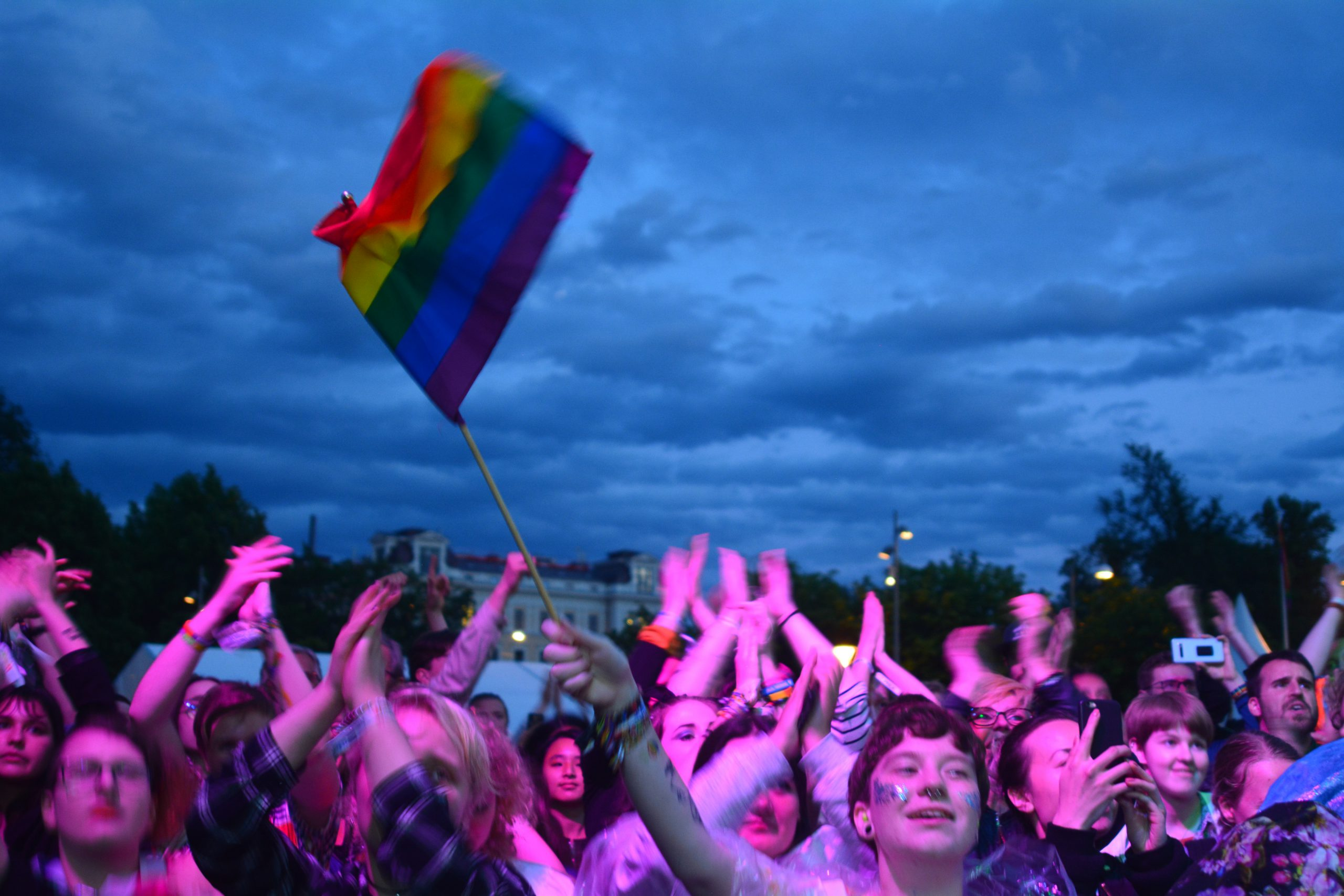 glada personer framför en scen tittar på ett uppträdande när det är kväll