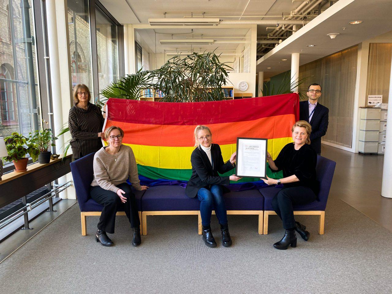 två personer håller upp en regnbågsflagga. tre personer sitter framför flaggan i en mörkblå soffa och visar upp ett HBTQ-diplom