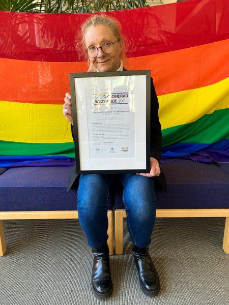 anna-carin jonsson håller upp hbtq-diplomet. bakm henne hänger en regnbågsflagga