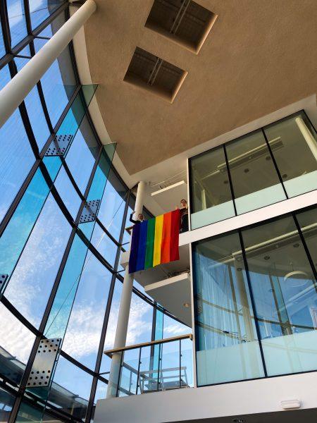 en regnbågsflagga är upphängd högt uppe i göteborgs uniersitets lokaler