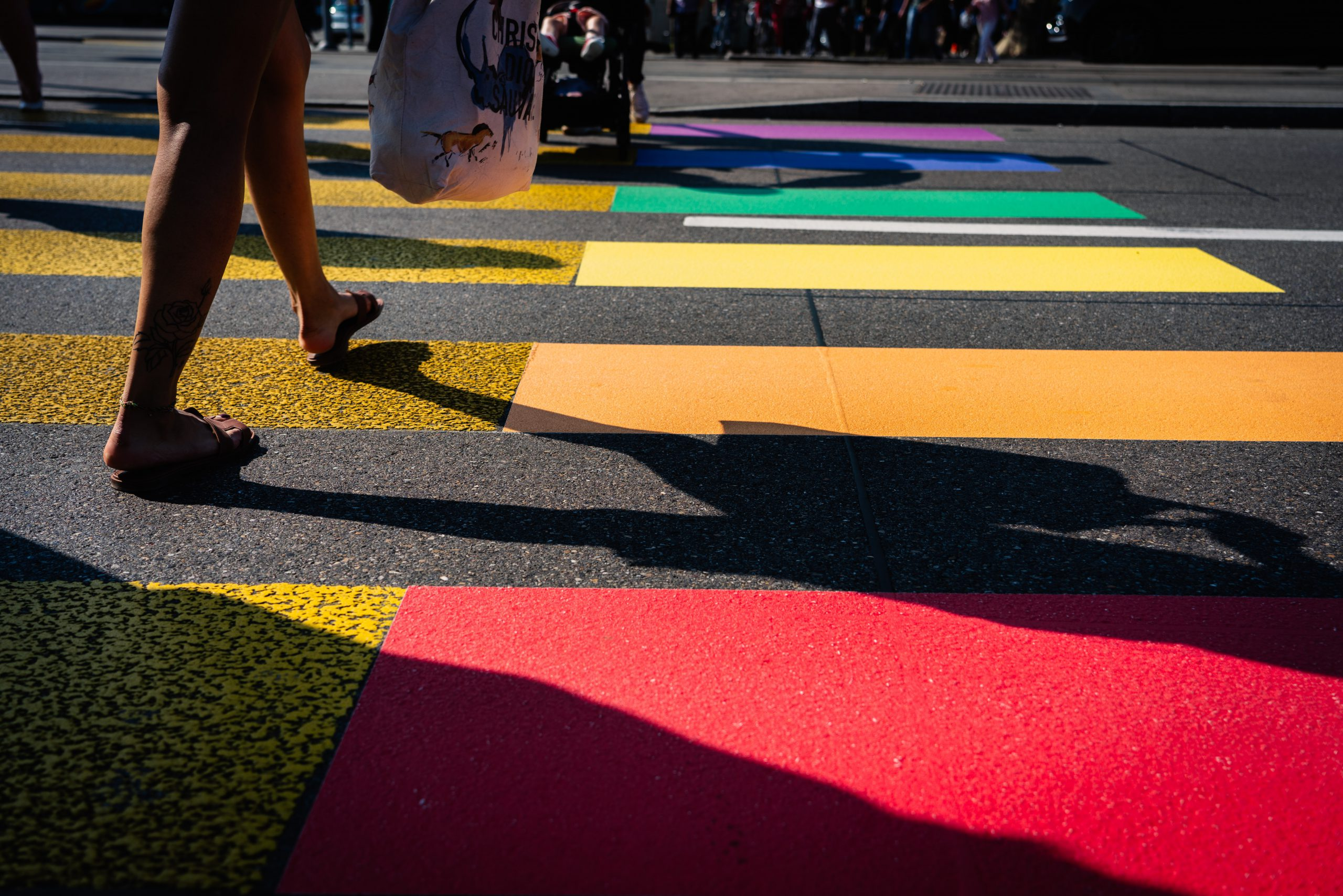 en person går över ett övergångsställe som är målat i regnbågens färger