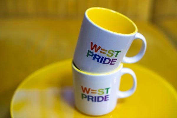två muggar med west prides logga står på ett gult bord