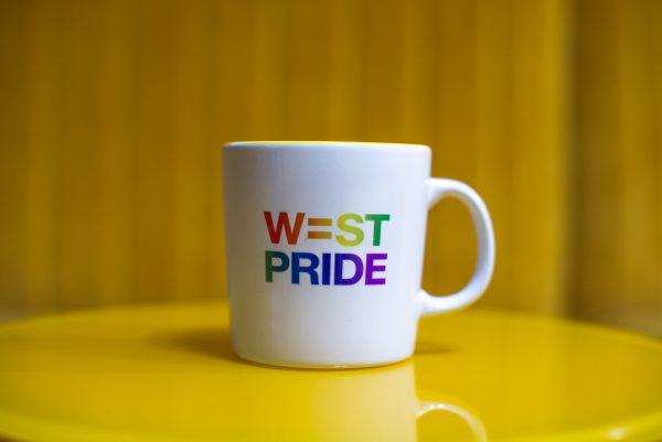 en mugg med west prides logga står på ett gult bord