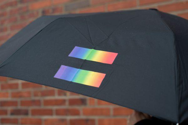 svart paraply med west prides logga på en av panelerna