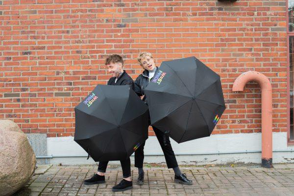 två personer står framför en tegelmur med varsitt svart paraply. west prides loggor är tryckt på paraplyets paneler.