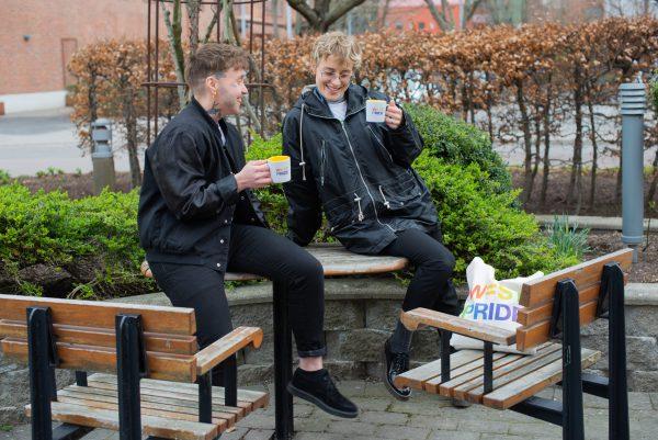 två personer i mörka kläder sitter utomhus på ett trädgårdsbord och håller i varsin mugg med west prides logga