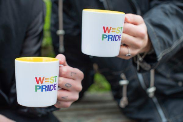 två personer håller i varsin mugg med west prides logga