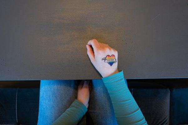 en person sitter i en soffa och har handen på bordet. på handens ovansida sitter en gnuggistatuering