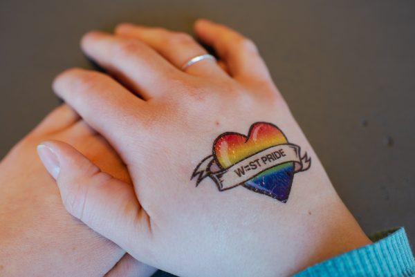 en person har en gnuggistatuering på handen. gnuggisen föreställer ett regnbågsfärgat hjärta med ett band över och på badnet står det west pride