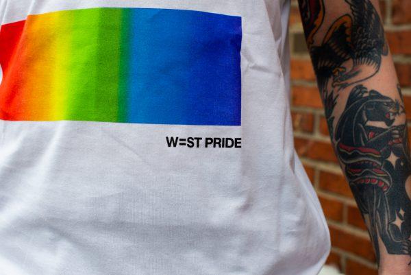 närbild på en vit west pride t-shirt som har west prides logga som tryck