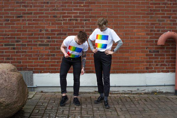 två personer står framför en tegelmur och har på sig varsin west pride t-shirt. T-shirten är vit med west prides logga på.
