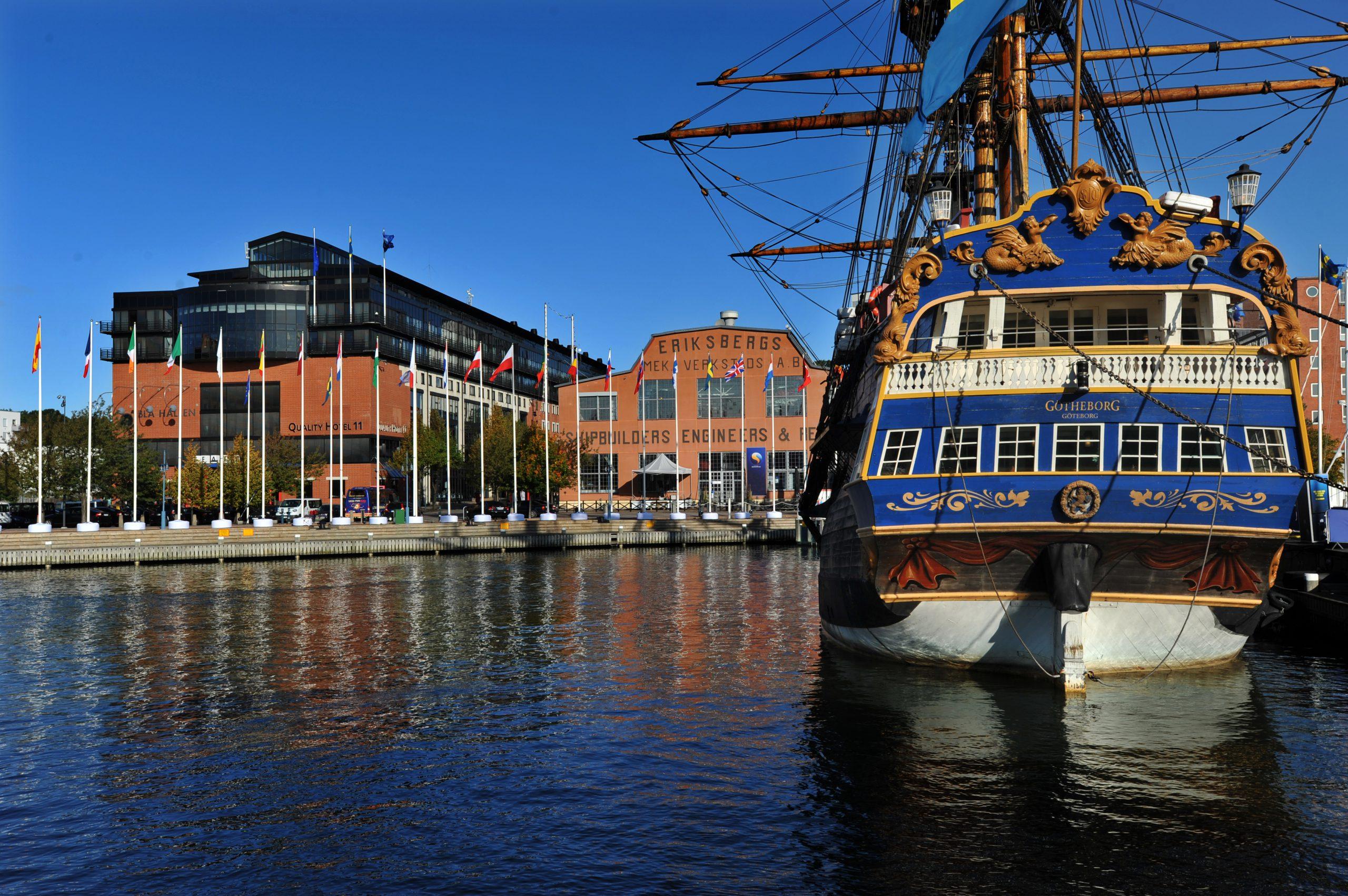 ett äldre segelfartyg ligger i hamnen framför eriksbergshallen som syns i bakgrunden