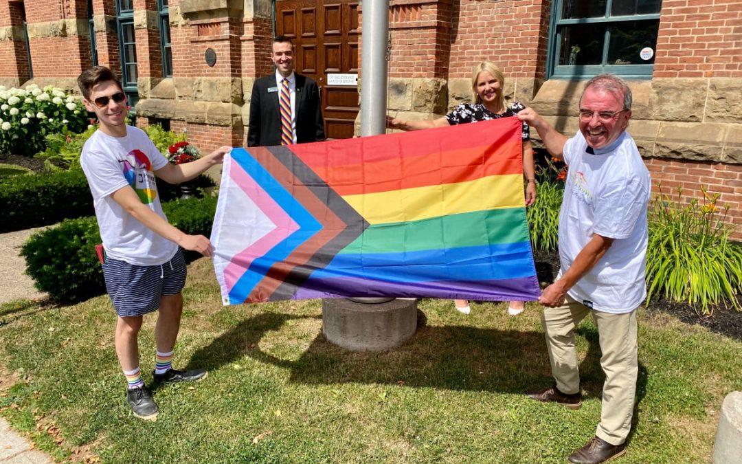 fyra glada personer håller upp framstegsflaggan