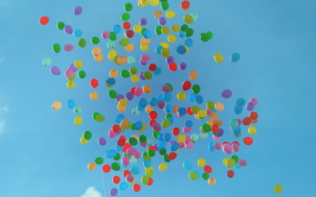 färgglada ballonger flyger högt upp i en blå himmel